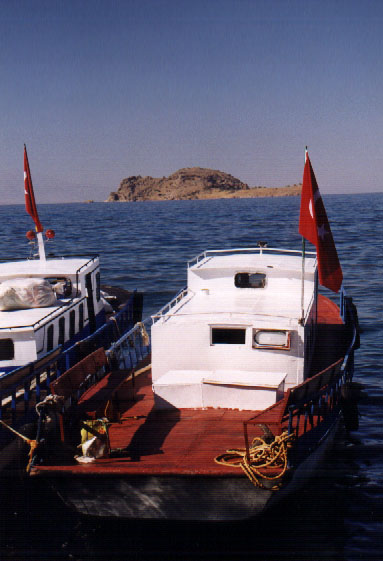 A boat is docked on shore across from Akdamar Island