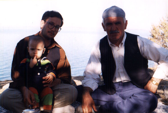 father, son and grandfather sit on a blanket drinking tea