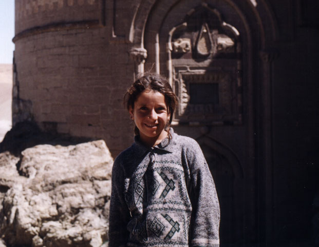 young girl in sweater poses in front of a castle wall