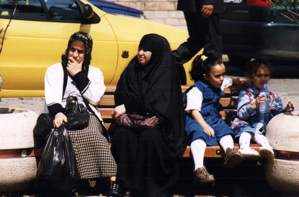 A woman in a black chador sits with her family